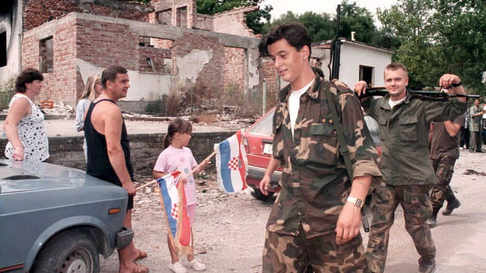 Horvatskie bežencы, vernuvšiesя v svoi doma, privetstvuюt horvatskih voennыh. 8 avgusta 1995 goda