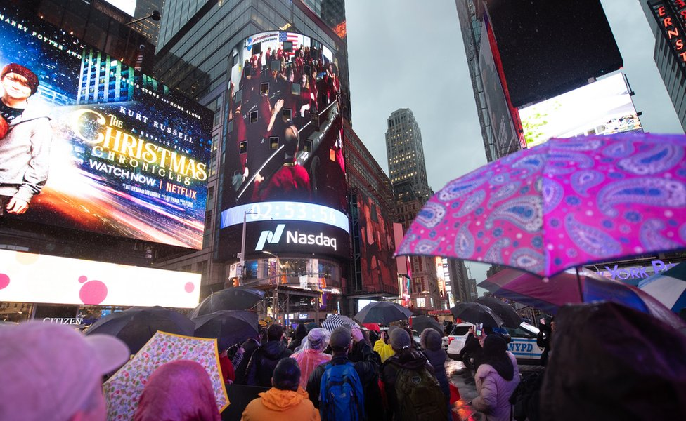 Spectators in Times Square watch the video