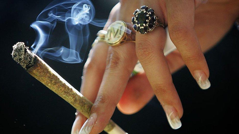 Mujer fumando marihuana.