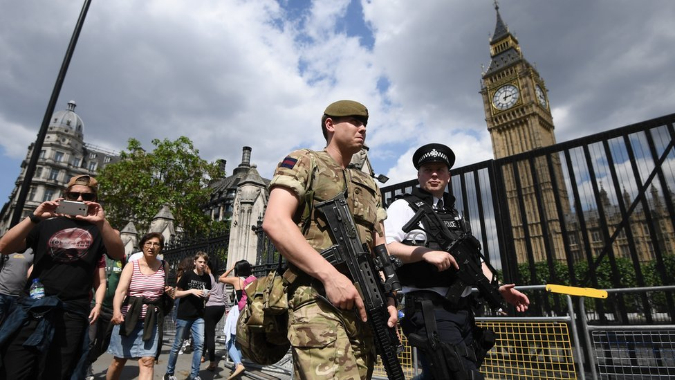 An armed soldier and an armed police officer patrol outside the Houses of Parliament on May 24, 2017 in London