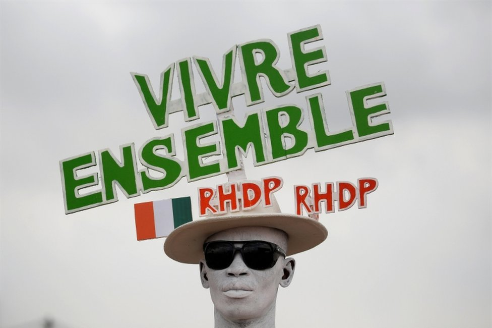 """A supporter with a painted face wears a hat with a slogan in relief during a campaign rally for the October 31, 2020 presidential election in Abidjan, Ivory Coast, October 17, 2020. The slogan reads """"Live together RHDP, RHDP""""."""