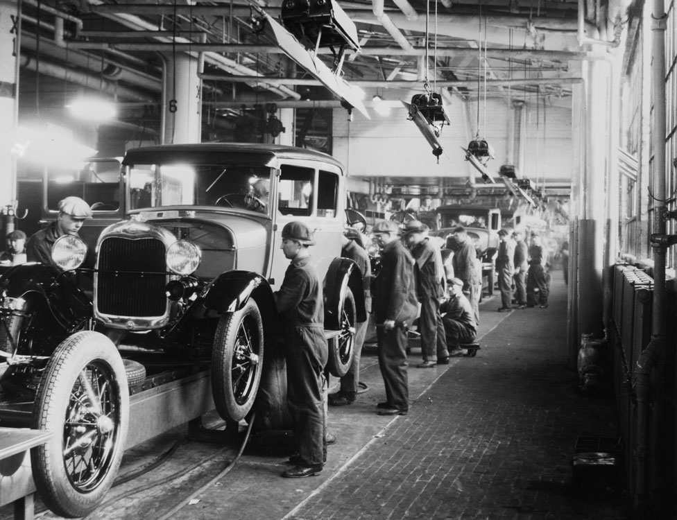 Assembly line workers inside the Ford Motor Company factory at Dearborn, Michigan pictured in 1928