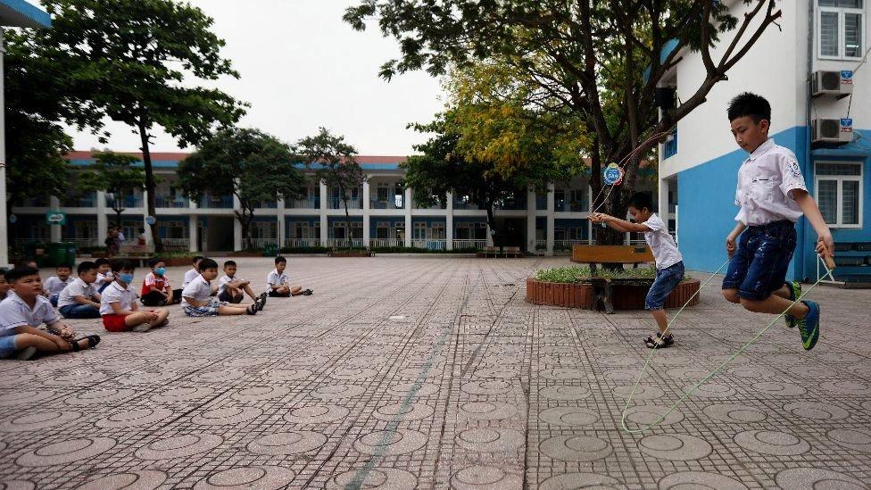 Crianças fazem ginástica no pátio da escola