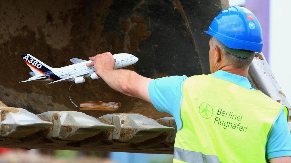 Un obrero sostiene un avión de juguete en el BER