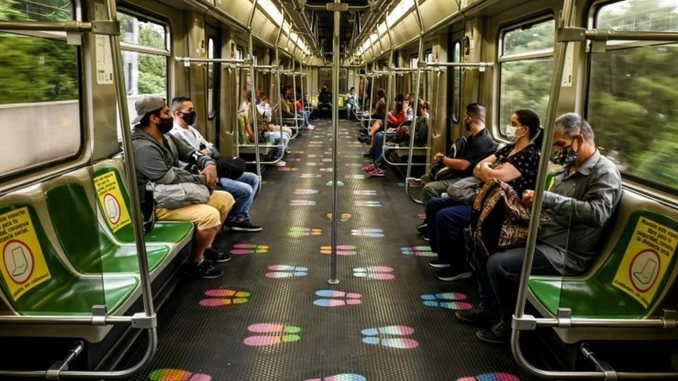 Commuters wear face masks and keep social distance as preventive measures against the spread of the COVID-19 coronavirus, on the metro in Medellin, Colombia, on June 17, 2020