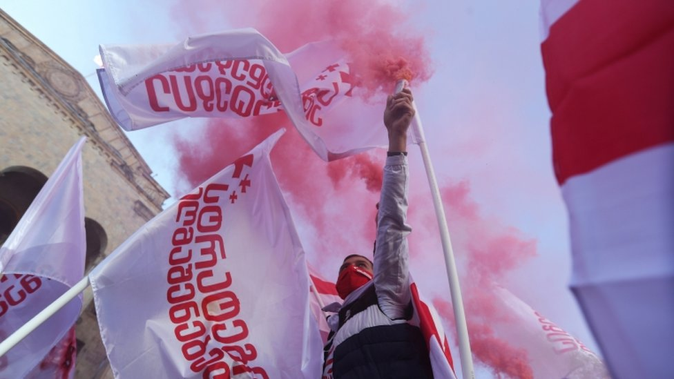 An opposition supporter holds a flare during a rally against the results of a parliamentary election in Tbilisi, Georgia