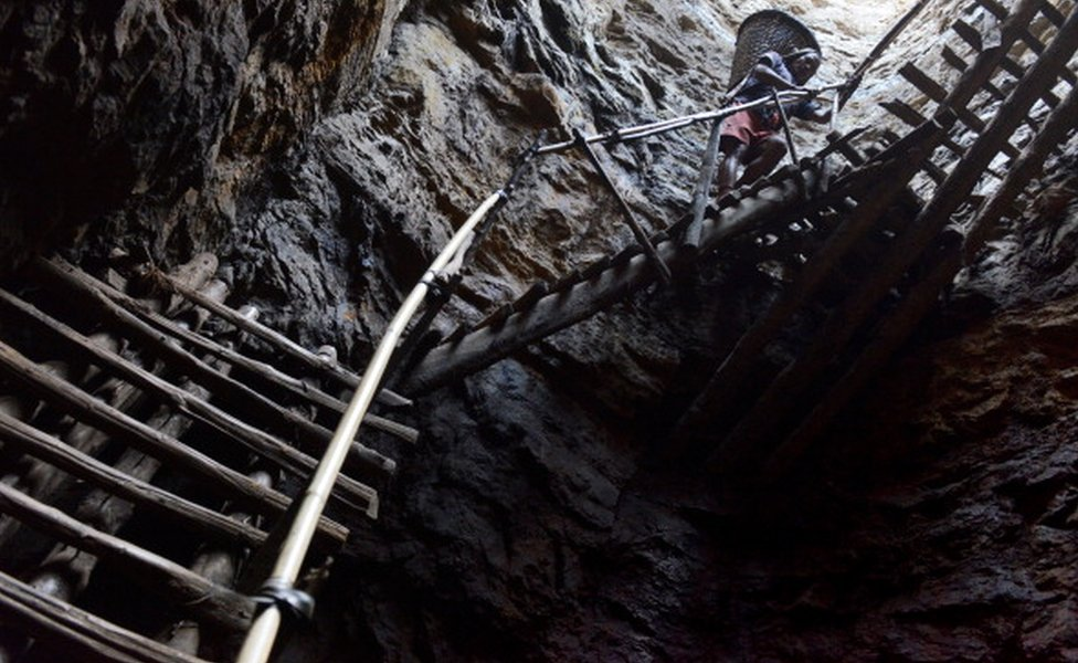 A miner Carries a heavy load of wet coal on a basket hundreds of feet up on wooden slats in a deep coal mine in Meghalaya.