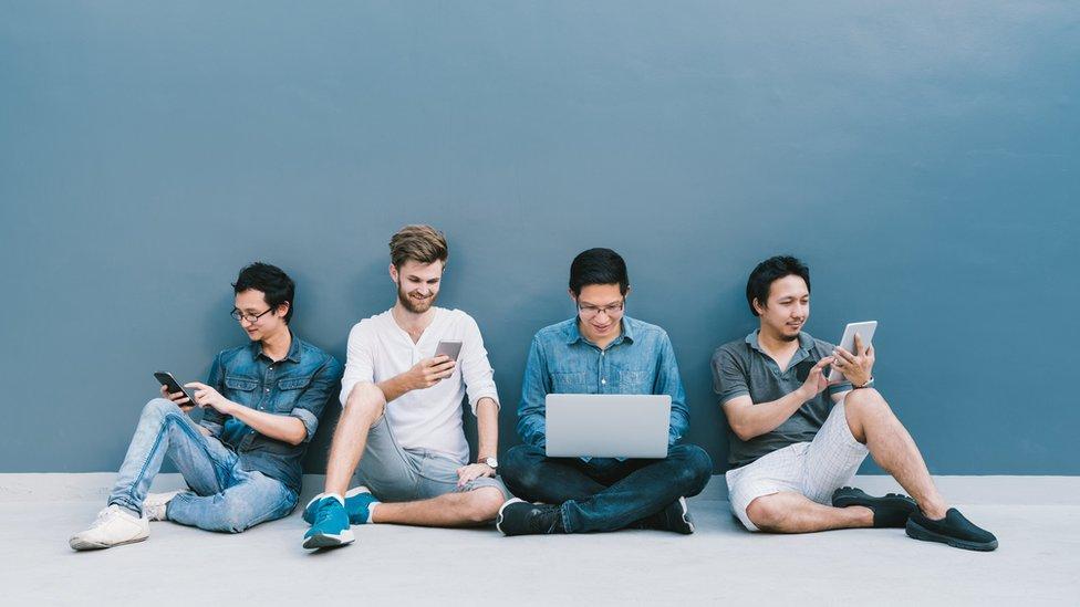 Cuatro hombres usando teléfonos y computadoras portátiles.