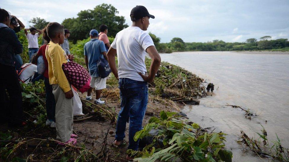 Hondureños mirando el río Goascorán.