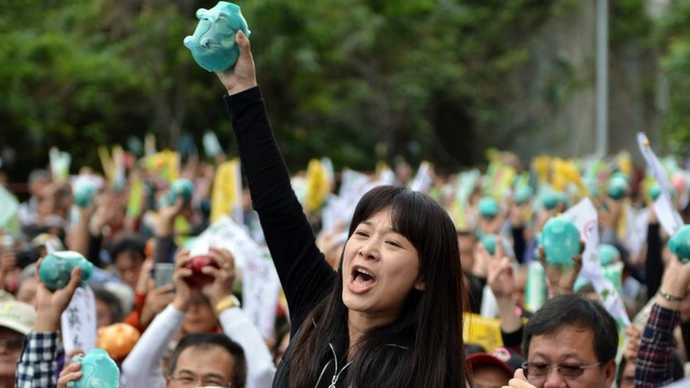 A supporter of Tsai Ing-wen (not pictured), chairwoman from Taiwan's main opposition Democratic Progressive Party (DPP) and the party's candidate for in the January 2016 presidential election, holds up a piggy bank at a party fundraiser