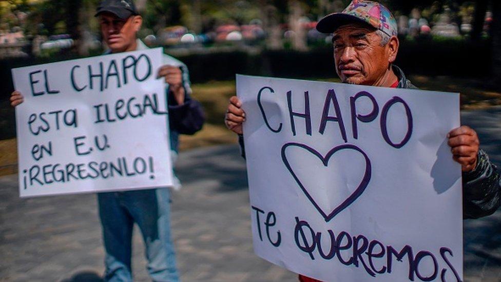 Dos hombres sostienen carteles alusivos a El Chapo