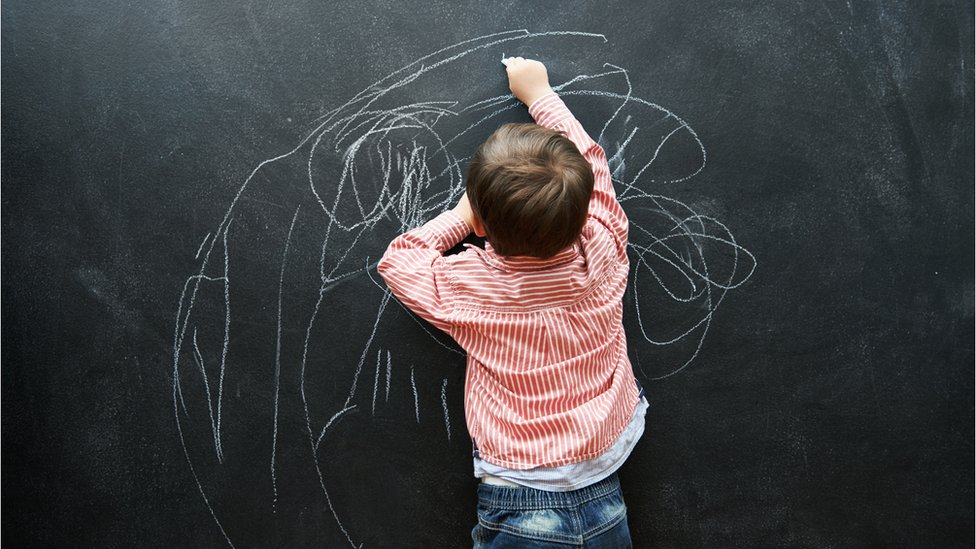 Niño dibujando con tiza.