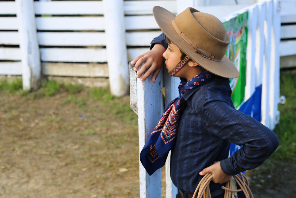 A young gaúcho watches a rodeo, lasso in hand