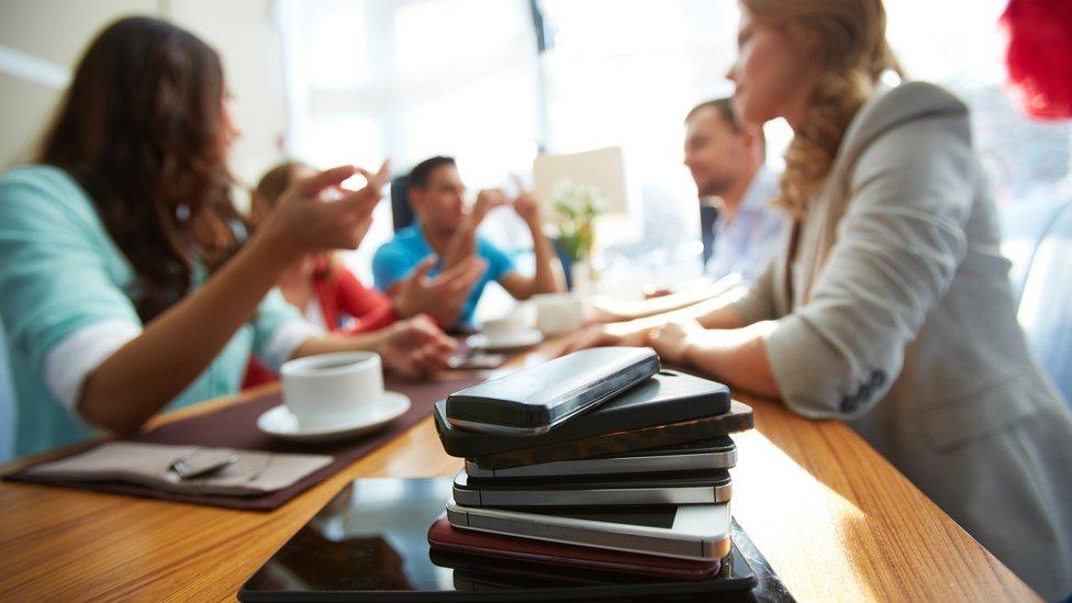 Pila de celulares en una mesa donde la gente habla