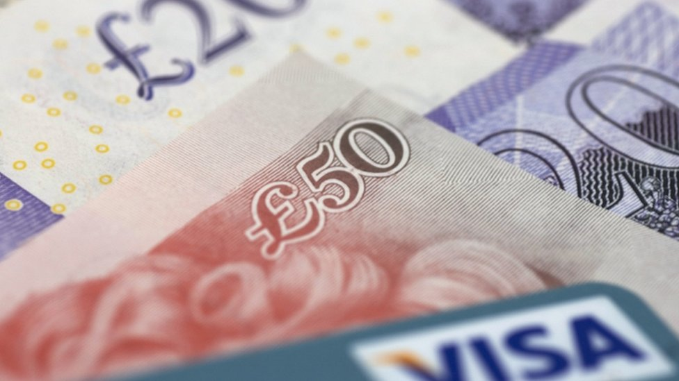 £20 and £50 note next to a Visa credit card
