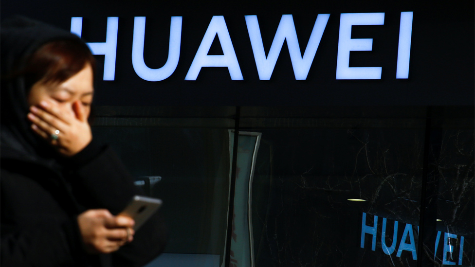 File image: A woman uses her phone as she walks past a Huawei shop in Beijing, China