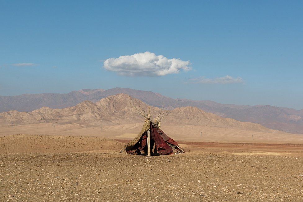 Tent in front of mountains, below a small white cloud in the sky