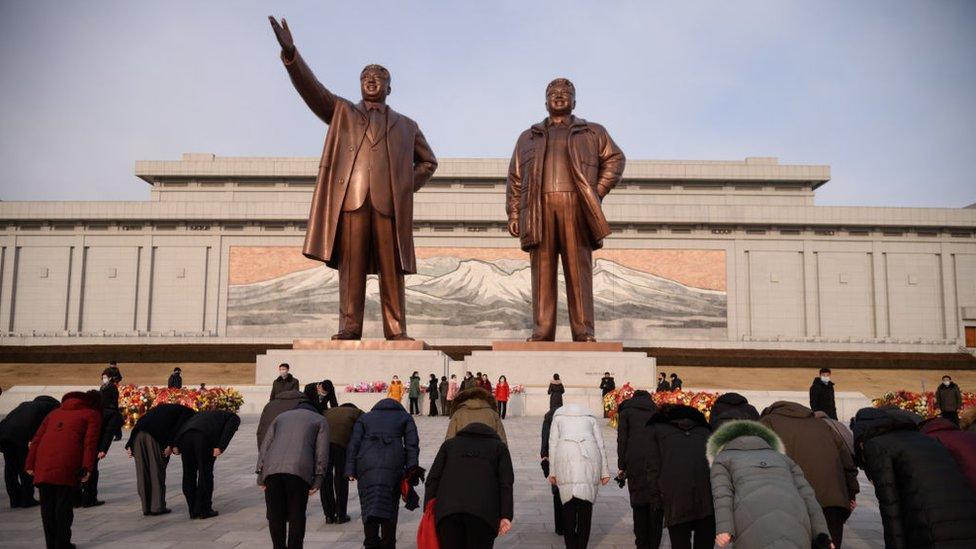 Visitantes hacen una reverencia ante las estatuas de los líderes Kim Il-sung y Kim Jong-il.