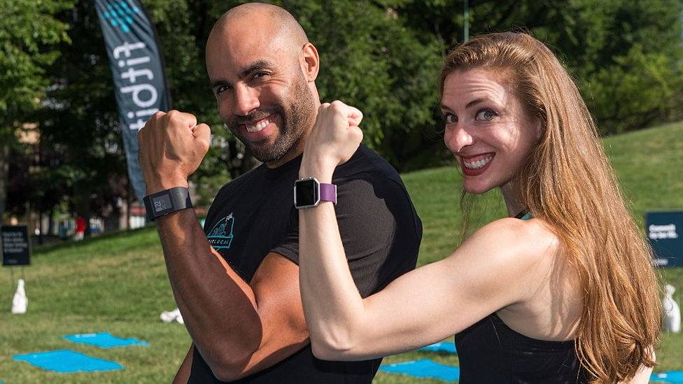 Man and woman wearing Fitbits