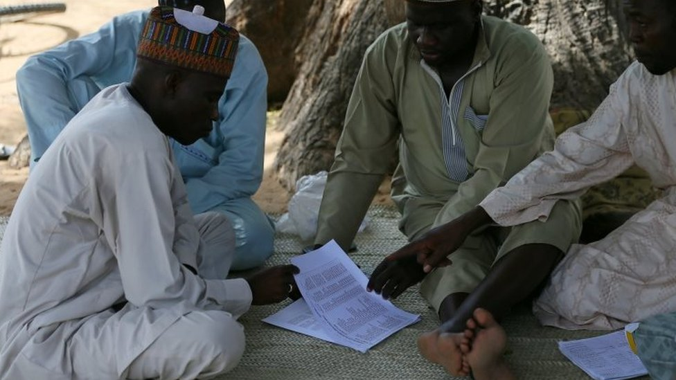 Parents of missing school girls check name lists in Dapchi. Photo: 23 February 2018