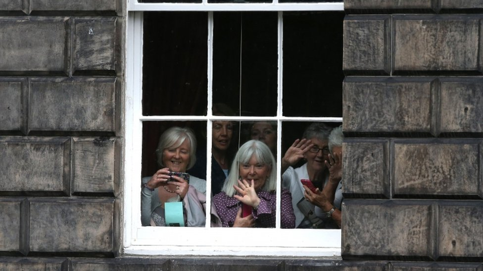 People look from a window as Theresa May leaves Bute House