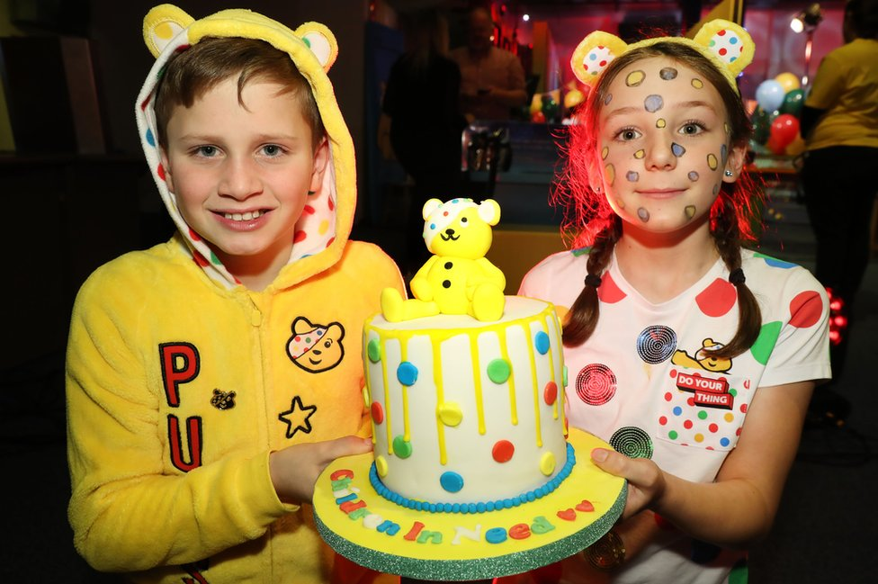 Two children hold a Childern in Need themed cake