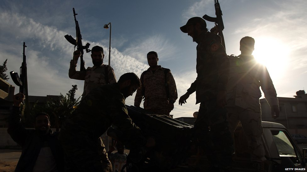 Members of a brigade headed by field commander Salah Bogheib and loyal to Khalifa Haftar hold up their guns as they fight alongside Libyan army troops against Islamist gunmen in the eastern Libyan city of Benghazi on December 17, 2014.