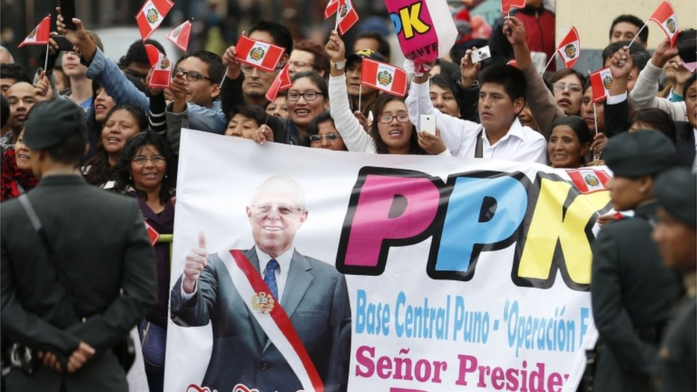 Supporters of Peru's president Pedro Pablo Kuczynski wave flags in the streets