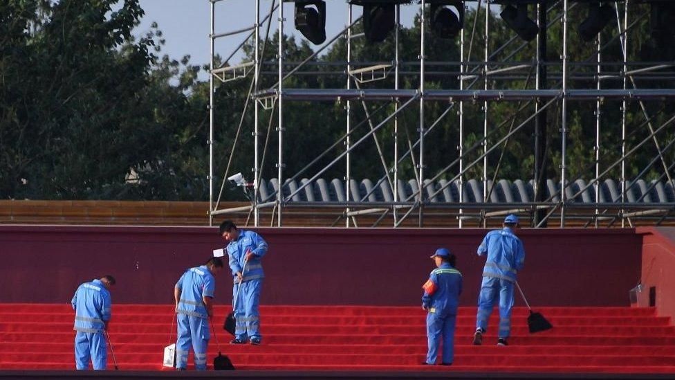 慶典彩排前,工作人員正在清理天安門附近的看台。