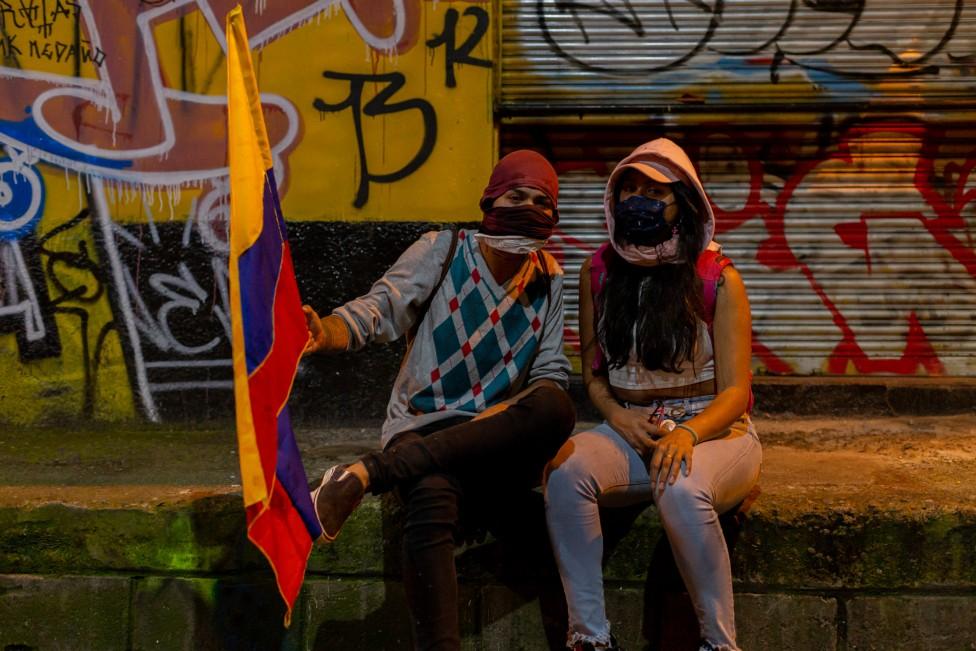 Dos mujeres con una bandera colombiana posan para una foto durante una protesta en Medellín, 19 de mayo de 2021
