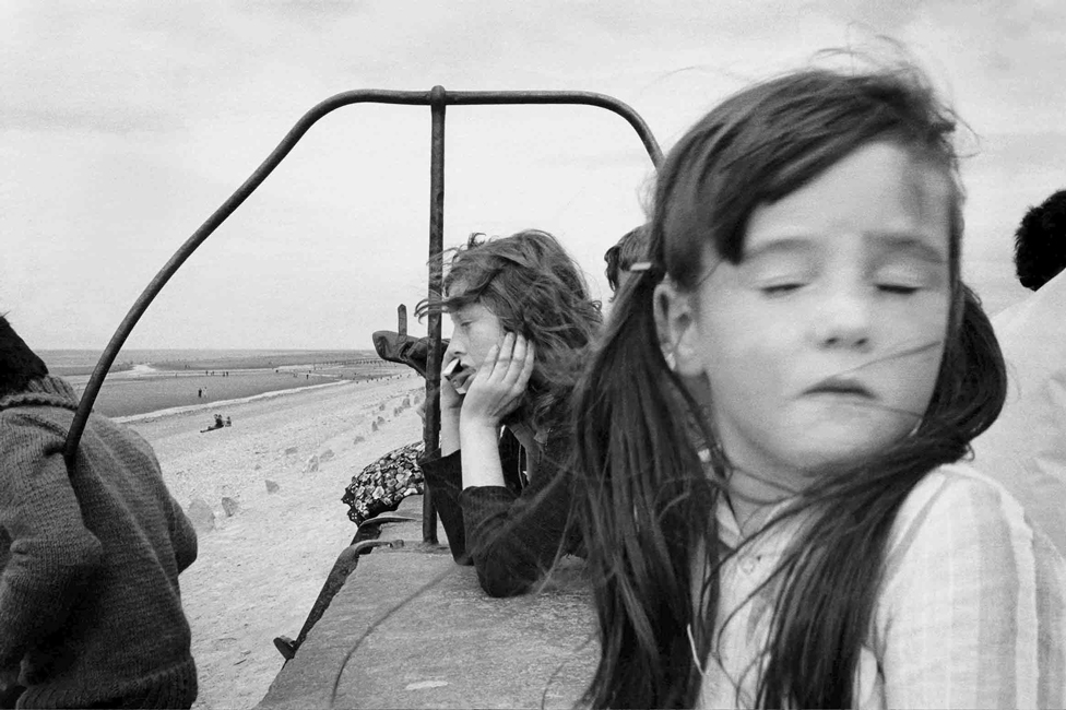 A young girl with eyes closed in front of a person looking at the sea, in Towyn