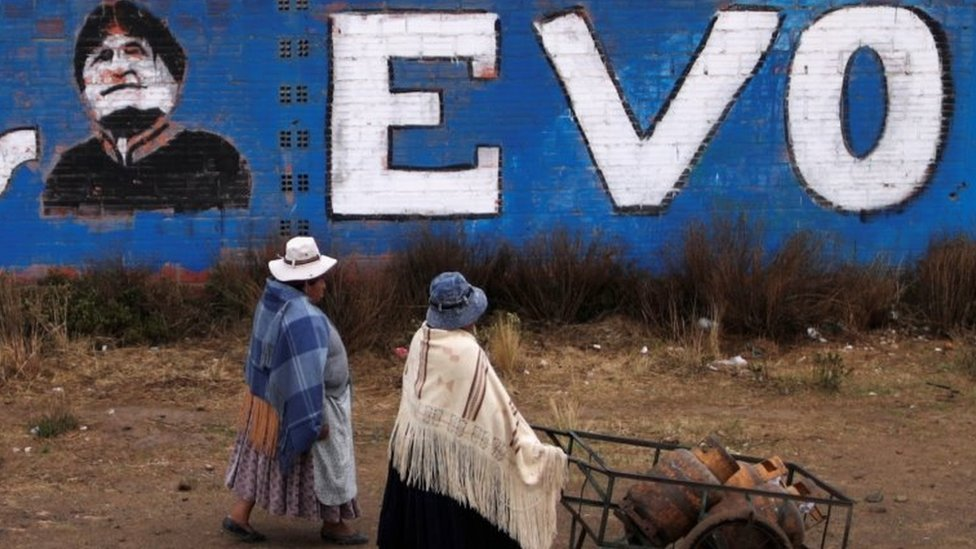 Women walk past a wall with a graffiti depicting former Bolivian President Evo Morales, before general elections in La Paz, Bolivia, October 17, 2020.