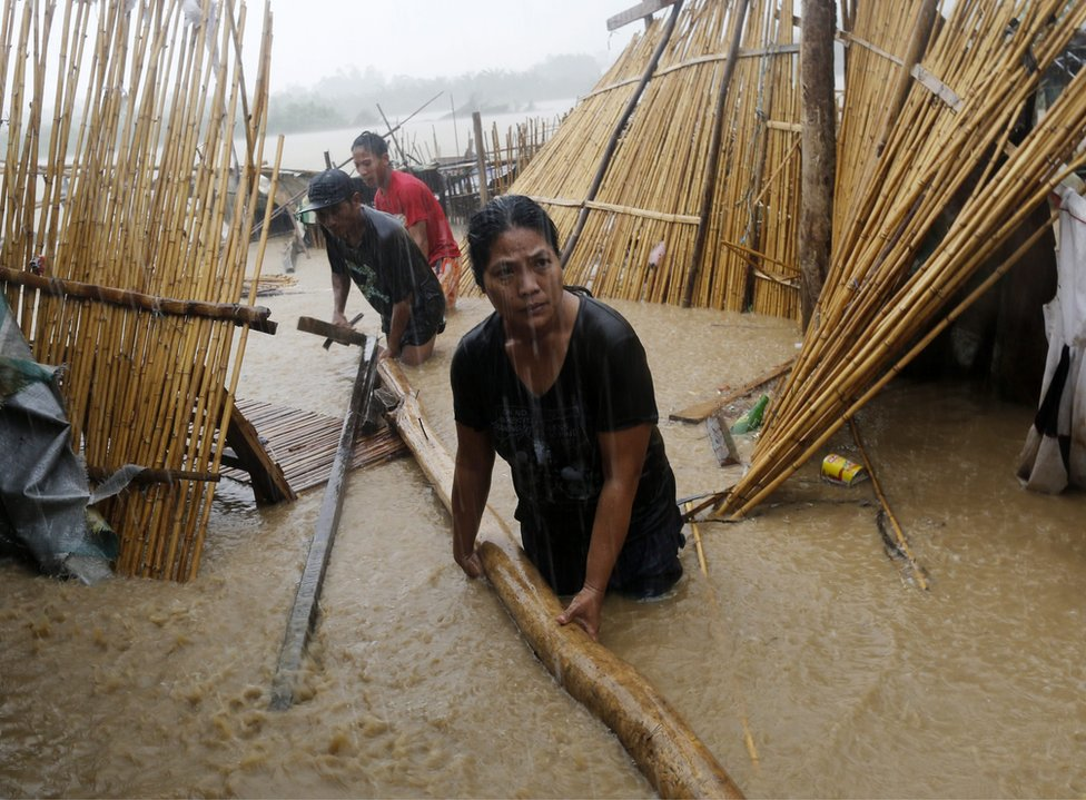 Filipino villagers collect house materials damaged by flood brought about by Typhoon Sarika in the town of San Leonardo, Nueva Ecija province, Philippines, 16 October 2016.