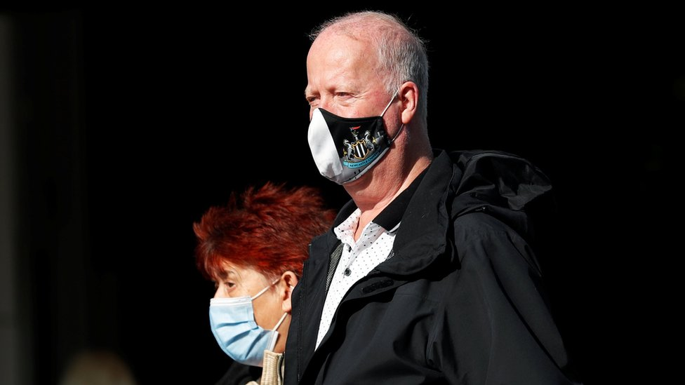 Man wearing a Newcastle United face mask