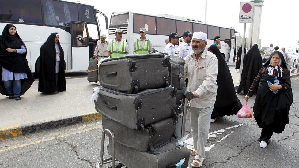 An Iranian pilgrim (C) returns from Saudi Arabia