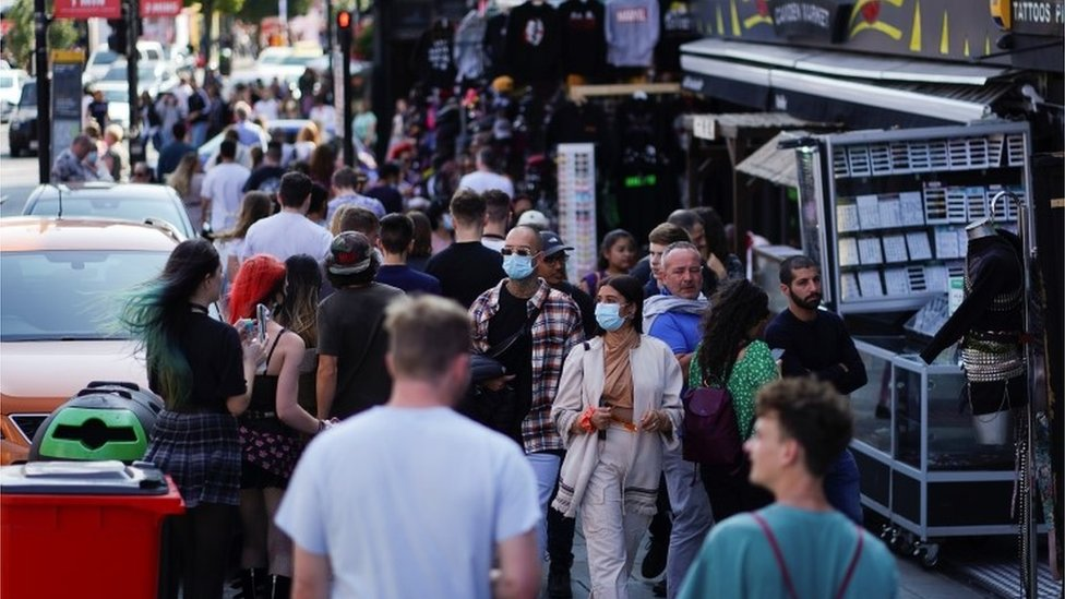 People walk along Camden High Street, amid the coronavirus disease