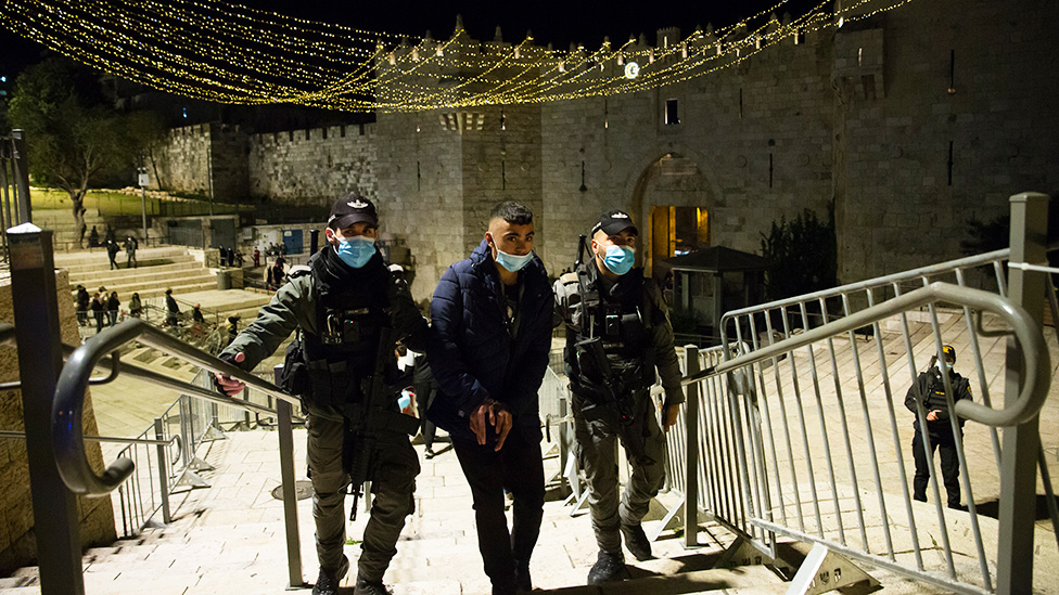 Israeli police officers detain a young Palestinian man at the Damascus Gate