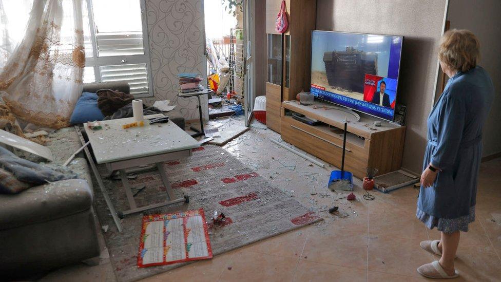 Una mujer israelí reacciona mientras comprueba los daños en el interior de su casa, alcanzada por los disparos de cohetes palestinos en la ciudad de Ashkelon, al sur del país.