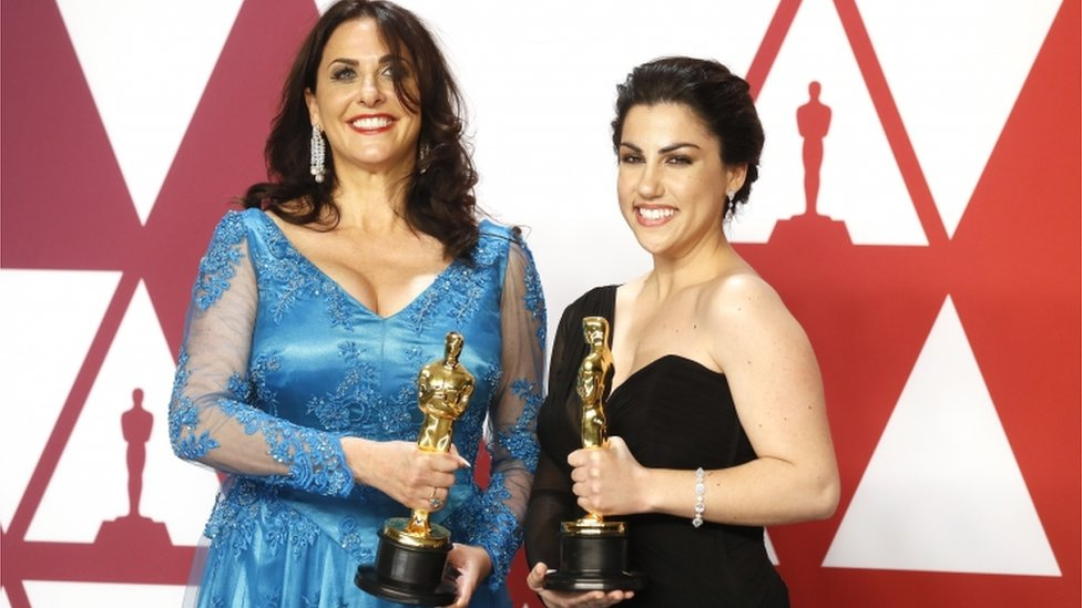 """رييكا زيتابشي، مخرجة """"الدورة الشهرية، نهاية الجملة"""" (إلى اليمين) ومليسا برتون، منتجته تحملان جائزة الأوسكار"""