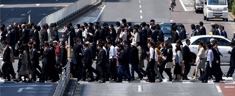 White-collar workers cross the road in Tokyo, Japan, on April 3, 2017.