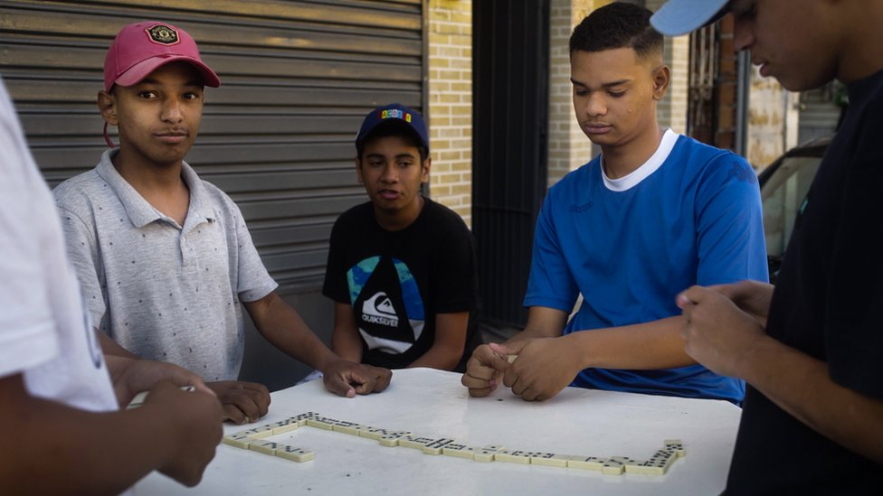 Teenagers move their domino game to the street during the coronavirus pandemic