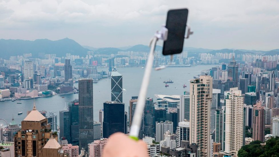 A tourist holds a selfie stick (C) from the peak which overlooks the city of Hong Kong and Victoria Harbour on June 9, 2018
