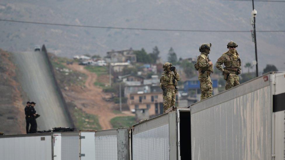 Militares de EE.UU. vigilan desde el muro fronterizo con México durante la visita de Donald Trump en marzo de 2018 a San Diego.