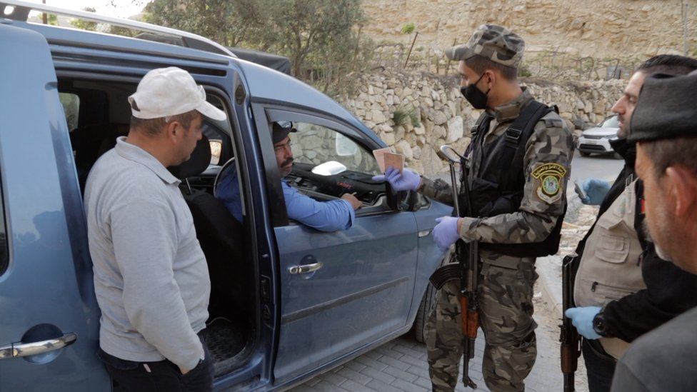Palestinian security forces search a car near the West Bank town of Hebron to prevent workers crossing illegally into Israel