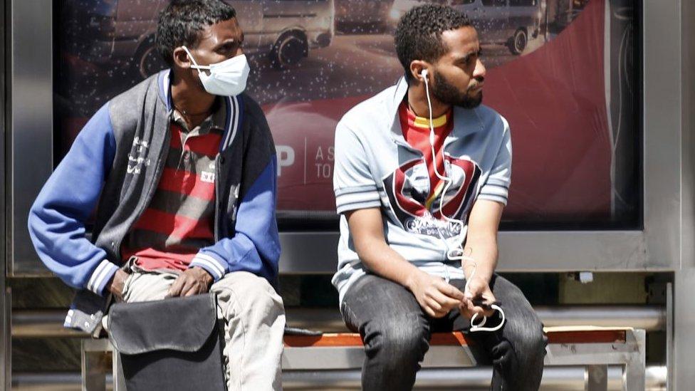 Dos personas en una parada de autobús en Etiopía.