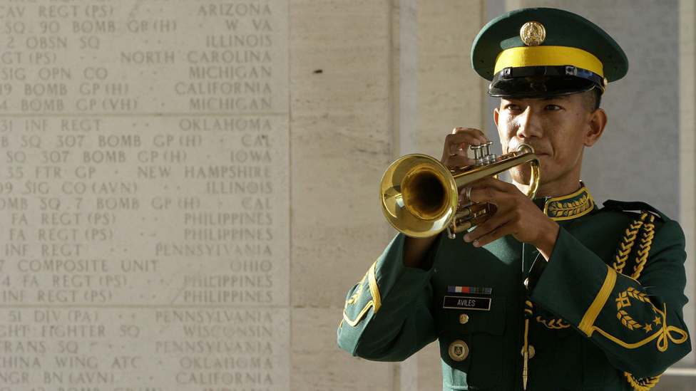 A Philippine army bugler plays beside a wall inscribed with names of fallen Filipino and American soldiers during a Memorial Day service at the American Cemetery in Manila, Philippines, on Monday, 31 May 2004