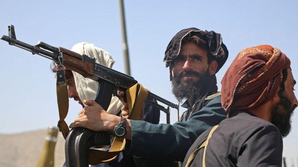 Três combatentes do Talebã, um deles armado e olhando em direção à câmera