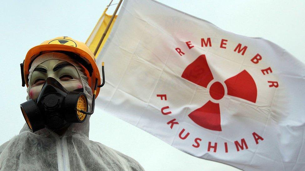 """Una persona porta una bandera con la leyenda """"Recuerda Fukushima"""""""