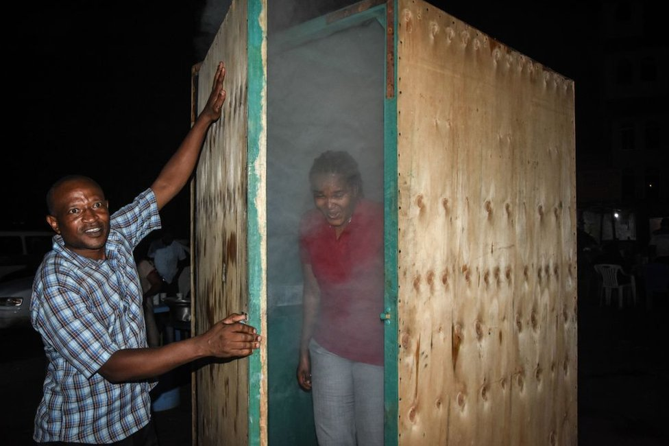 A woman is shrouded in steam as she leaves an inhalation booth installed by a Tanzanian herbalist.