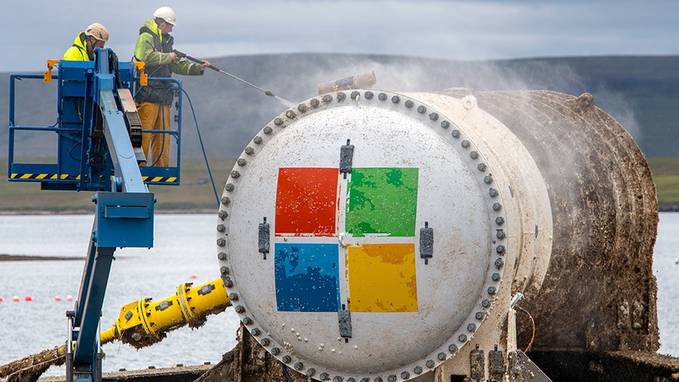 Two men power-wash the exterior of the Microsoft data centre capsule